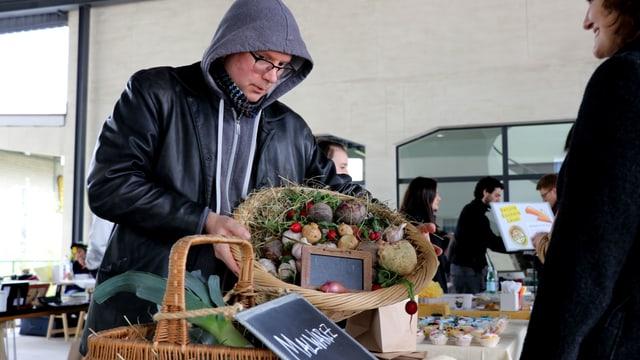Ein Mann mit schwarzer Jacke und Kapuze hält einen Gemüsekorb in den Händen.
