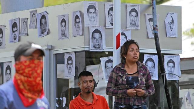 Angehörige vor an einer Wand aufgehängten Suchbildern der Studenten.