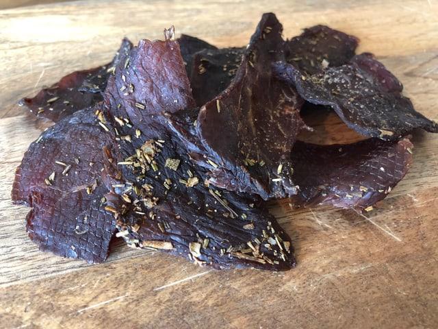 Getrocknetes Fleisch auf einem Holzbrett.