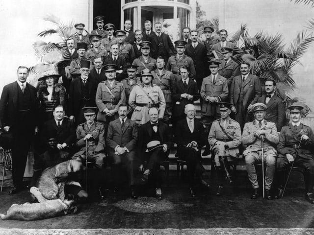 Gruppenbild mit mehrheitlich Männern in teils militärischen Anzügen.