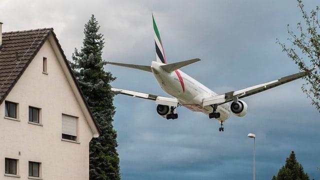 Ein Flugzeug fliegt über ein Wohngebiet in Kloten.
