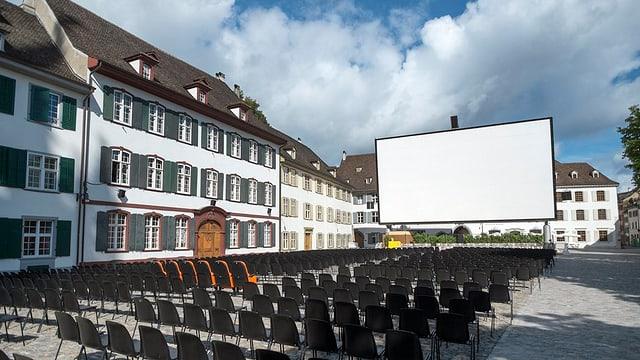 Münsterplatz in Basel. Man sieht eine grosse, weisse Leinwand und viele Stühle, die in Reihen vor der leinwand aufgestellt sind.