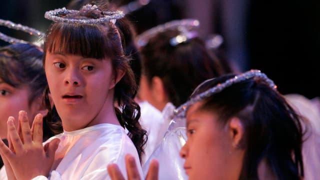 Behinderte Mädchen mit Kopfschmuck in weissen Kleidern falten die Hände.