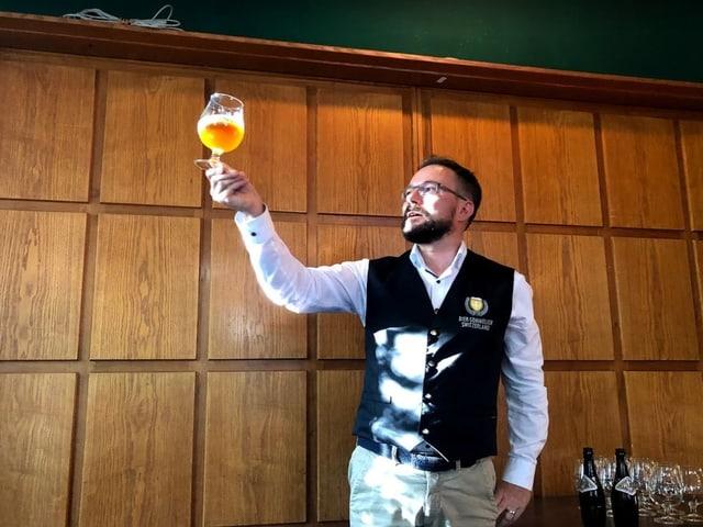 Ein Mann hält ein Bier empor,