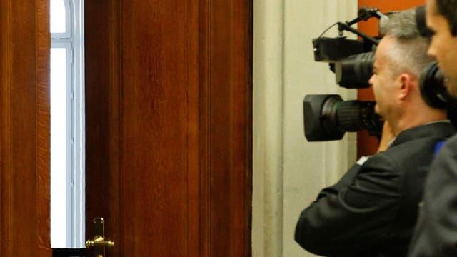 Journalisten im Bundeshaus vor einer halb verschlossenen Türe.