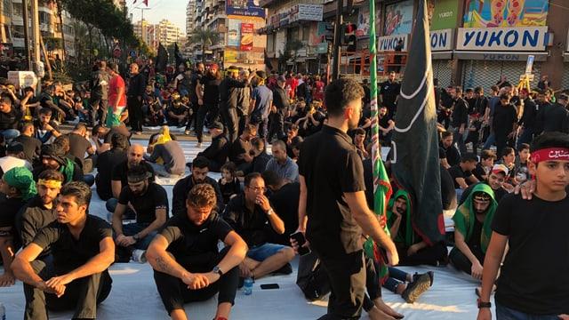 Hisbollah-Anhänger warten in den Strassen Beiruts auf den anstehenden Marsch.