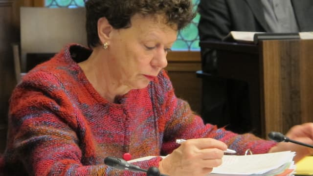 Esther Gassler sitzt im Raatssaal und blick konzentriert auf ihre Unterlagen.
