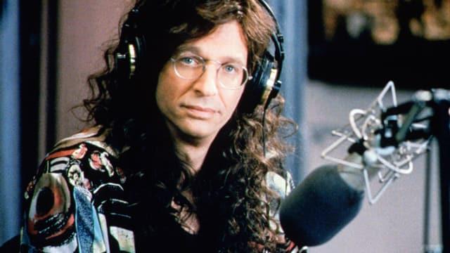 Ein Mann mit Brille und langen Haaren sitzt vor einem Mikrophon und schaut in die Kamera.