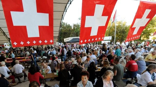 Festbänke stehen auf einem Platz, alle sind gut gefüllt. Über den Köpfen der Leute hängen drei Schweizerfahnen.