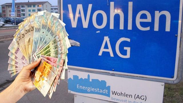 Eine Hand hält ein Bündel Banknoten, im Hintergrund Ortsschild von Wohlen.