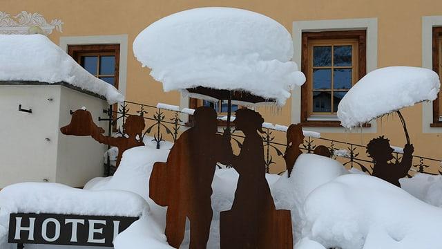 Tiefverschneiter Hoteleingang im Dorfkern von Müstair