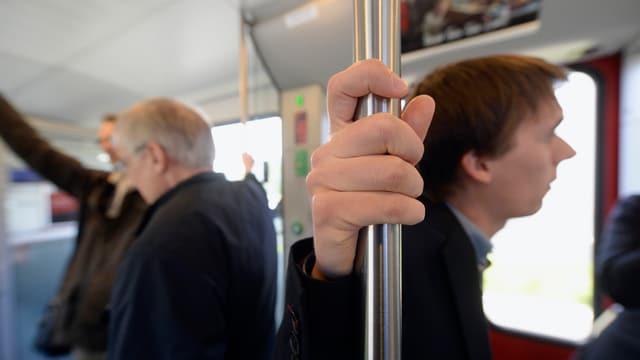 Ein Mann hält sich an einer Stange in einem Bus fest.