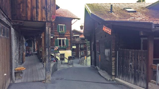 Enge Strasse durch alte Bündner Holzhäuser.