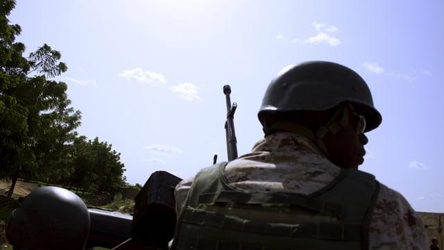 Ein bewaffneter Soldat von hinten fotografiert.