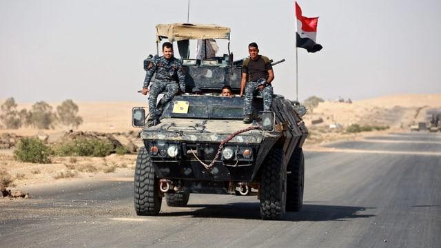 Mehrere irakische Soldaten auf einem Panzerwagen mit irakischer Fahne.