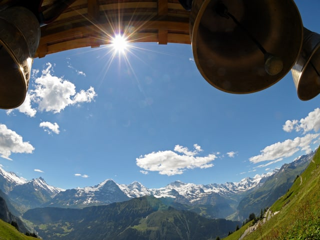 Oben im Bild ein Balken mit Glocken, die Sonne scheint unter dem Balken durch. In der Mitte ist blauer Himmel und unten das Alpenpanorama mit Schneebergen.