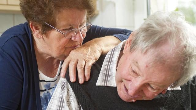 Ältere Frau pflegt liebevoll einen älteren Mann