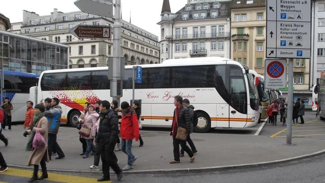 Toruisten vor parkierten Reisecars