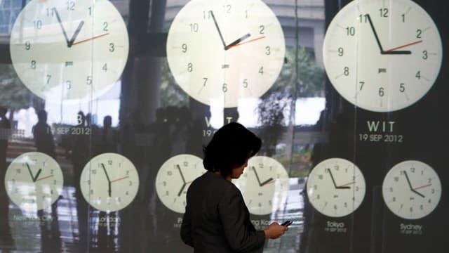 Eine Frau schaut auf ihr Handy, im Hintergrund sind in einem Schaufenster neun Wanduhren zu sehen, welche die unterschiedlichen Uhrzeiten an verschiedenen Orten der Welt zeigen.