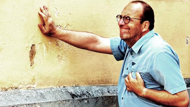 Mann greift sich mit schmerzverzerrter Mine an die Brust.