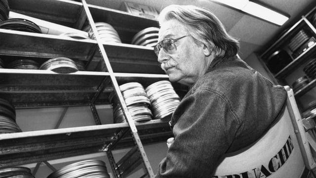 Ein Mann sitzt im Archiv, auf den Gestellen liegen viele Filmkassetten.