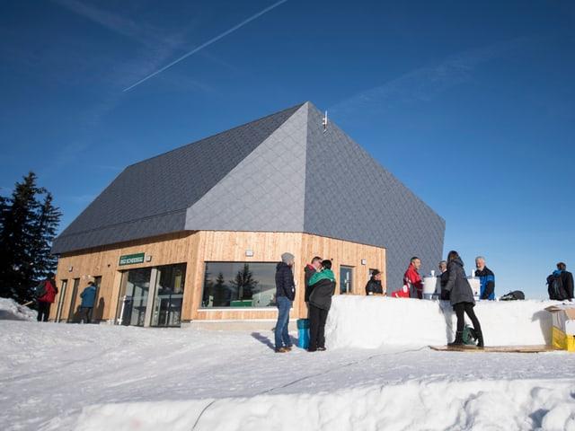 Die Bergstation auf Rigi Scheidegg mit Leuten an einer Schneebar.