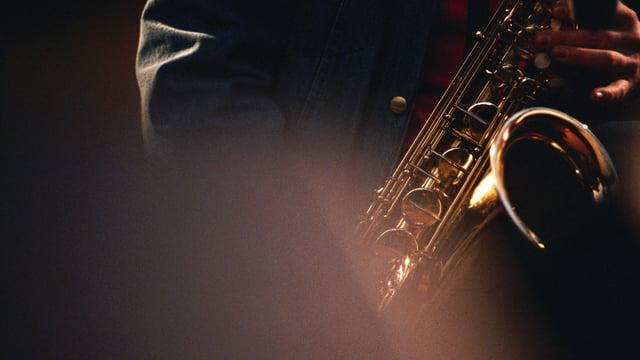 Jemand spielt Saxophon im Halbdunkeln der Bühne