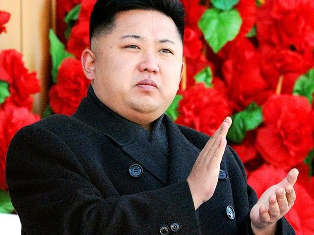 Kim Jong Un klatscht vor einem Blumenfenster.