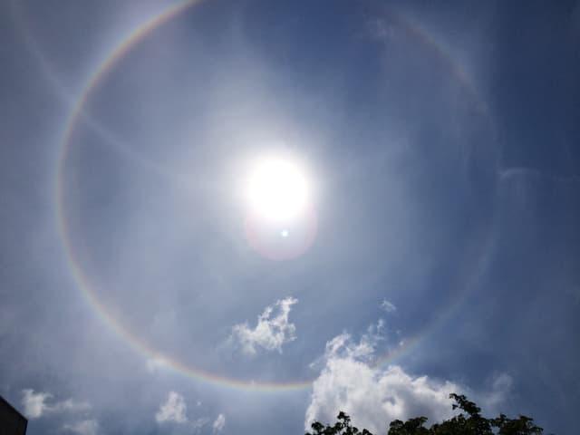 Milchig-blauer Himmel mit Sonnenscheibe in der Mitte. Um die Sonne ist ein feiner Kreis in allen Regenbogenfarben zu sehen.