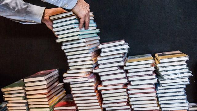 Eine Hand stapelt Bücher.