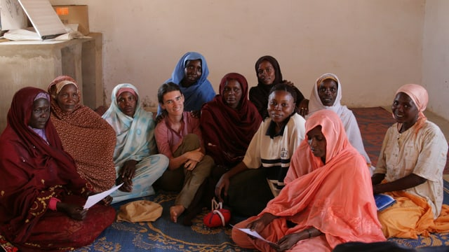 Nelly Staderini inmitten einer Gruppe afrikanischer Frauen sitzend