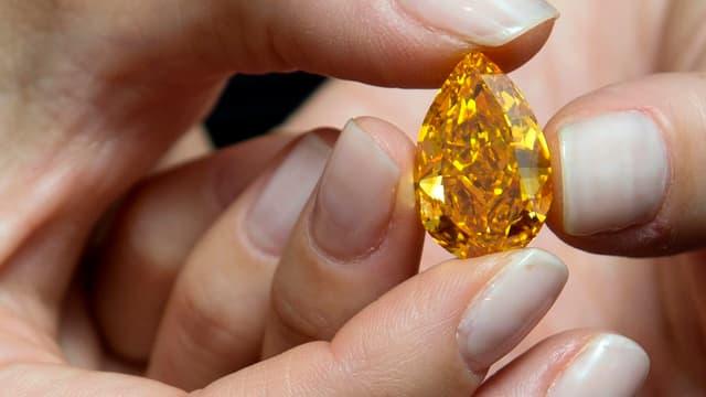 Der orange farbene Diamant zwischen Damenfingern. Seine Form jene eines Tropfens.