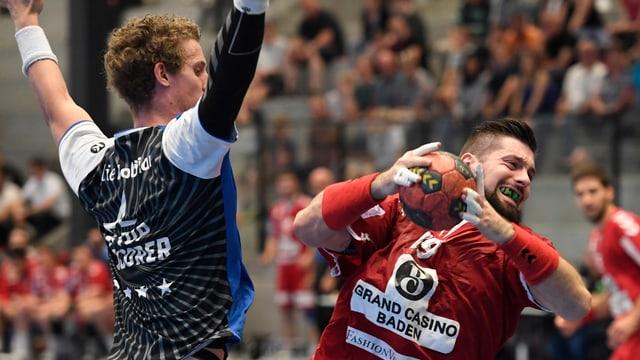 Mann in rotem Shirt hält Handball, Mann im schwarzen Shirt reisst Arme in die Luft.