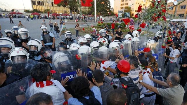 Demonstranten werfen Nelken