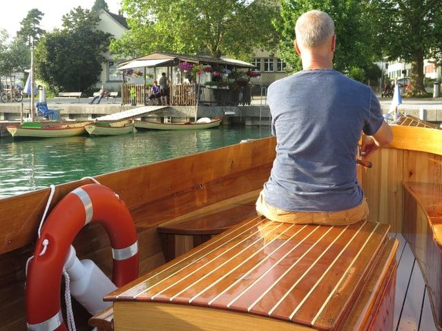 Mann steuert Motorboot auf Ufer zu