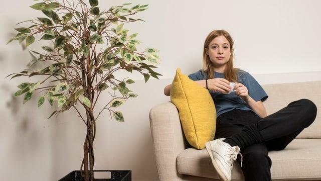 EIne Frau sitzt mt einer TAsse auf einem Sofa