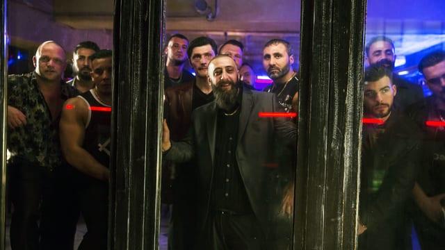 Ansicht durch ein Fenster, hinter der Scheibe steht eine grosse Gruppe dunkel gekleideter Muskelprotze und schaut raus.