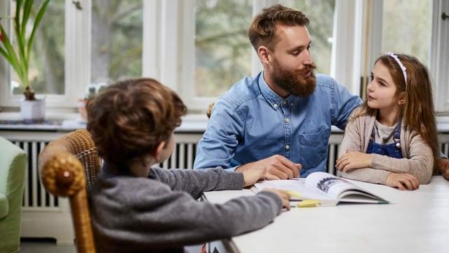 ein Mann mit zwei Kindern am Tisch