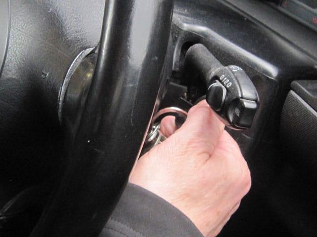 Nahaufnahme einer Hand, die einen Zündschlüssel im Auto dreht.