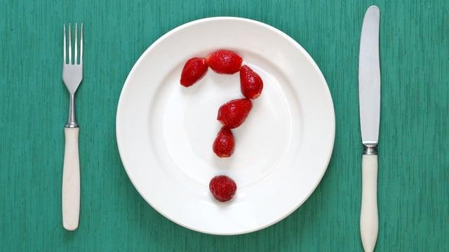 Weisser Teller mit Besteck. Auf dem Teller ist aus Erdbeeren ein Fragezeichen geformt.