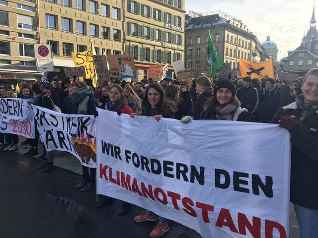 Menschenmenge auf grossem Platz. Schülerinnen halten Transparent: «Wir forden den Klimanotstand».