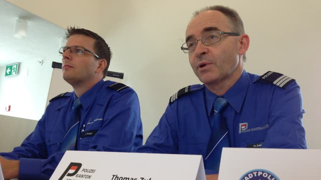 Harry Niggli sitzt neben Thomas Zuber, beide tragen ihre Uniform, vor sich haben sie Namenskärtchen. Im Vorderung ist auch eine Namenskärtchen mit dem Wappen der Stadtpolizei Olten.