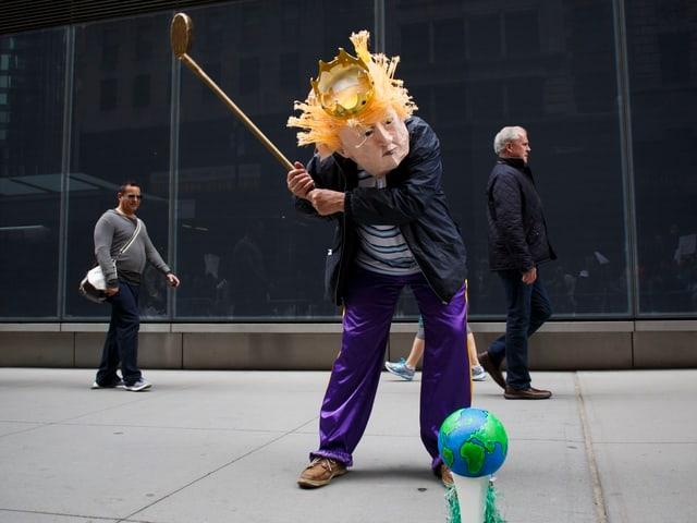 Ein Mann, verkleidet als Donald Trump, spielt Golf mit einer kleien Weltkugel.