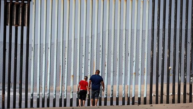 Zwei Personen vor dem Grenzzaun zwischen Mexiko und den USA