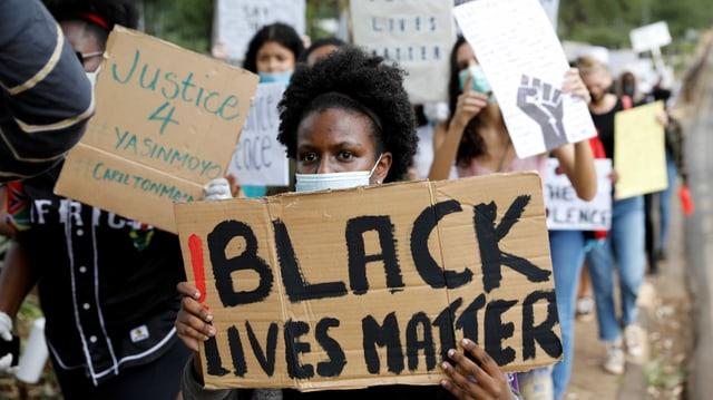Eine Dmo mit jungen Schwarzen und Black-Lives-Mätter-Parolen auf Kartons.