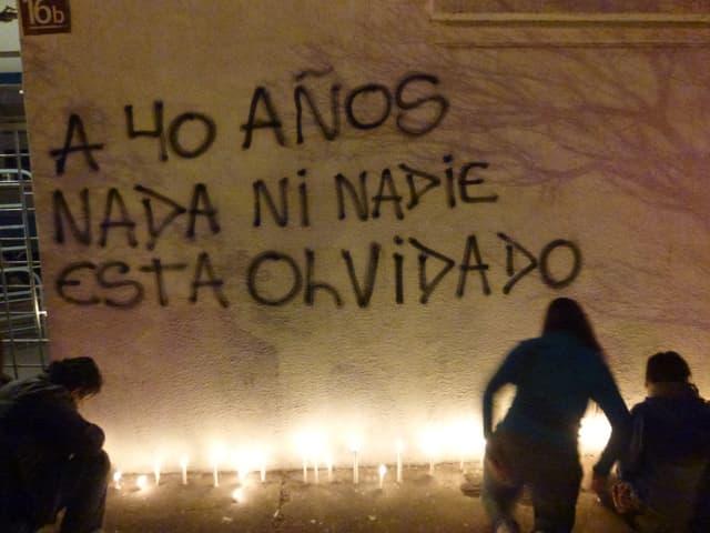 Graffiti an einer Wand: «Nach 40 Jahren: Nichts und niemand ist vergessen.». Am Boden scheinen Kerzen.
