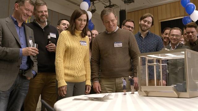 Eine Gruppe normalgrosser Menschen steht um einen Tisch. Sie alle tragen Namensschilder, im Hintergrund sind Ballons zu sehen. Auf dem Tisch stehen ein winziger Mann und eine winzige Frau, die durch ein Megaphon zu den Grossen emporrufen.