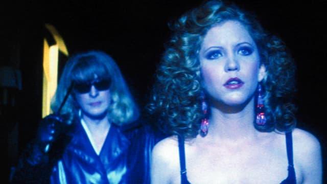 Eine Frau mit einem Funkgerät in der Hand, steht hinter einer anderen Frau.