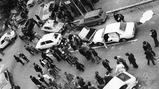 Mehrere Leute stehen um ein paar Autors herum, die quer auf einer Strasse stehen.