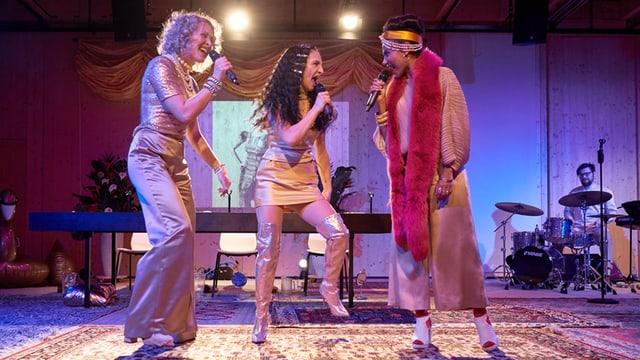 Drei Sängerinnen, im Hintergrund ein Schlagzeuger